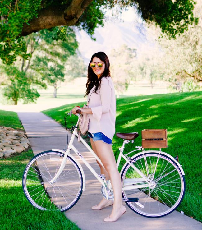 Kendi Everyday wears blush bell sleeve top, riding bikes in Ojai, California