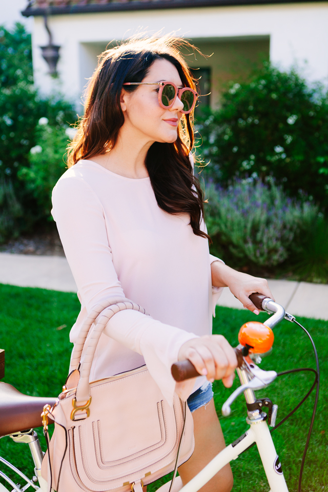 Kendi Everyday wears blush bell sleeve top, riding bikes in Ojai, California