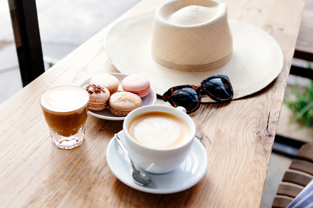 Macrons and coffee with summer hat and sunglasses