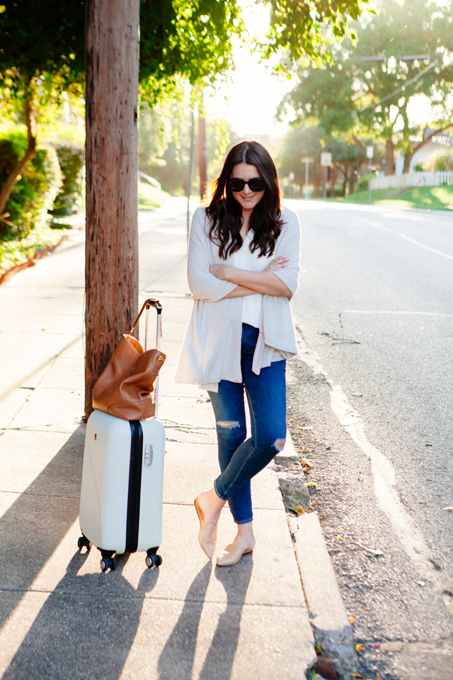 Travel outfit featuring an oatmeal sweater with distressed denim and nude flats, with a white carry-on. As seen on Kendi Everyday