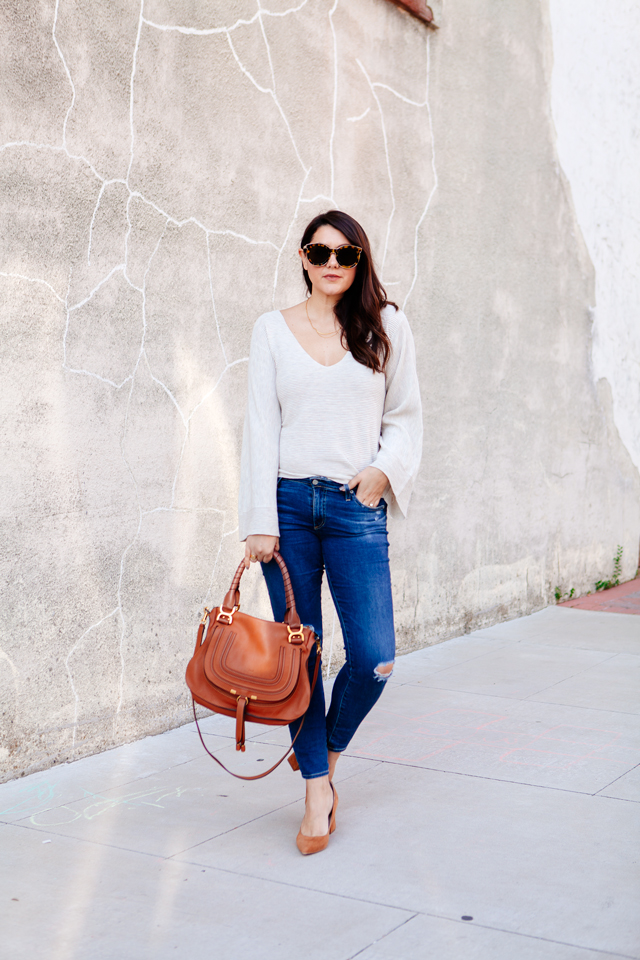 Bell sleeve sweater with skinny jeans and cognac accessories.