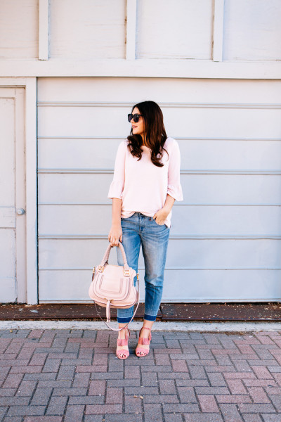 Pink Bell sleeve sweater with raw edge denim and madewell tassel pink suede heels.