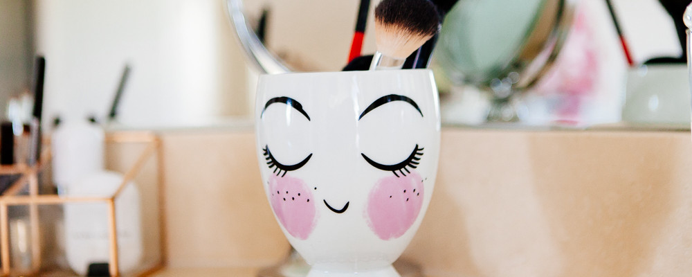 Painted lady ceramic cup for makeup brushes.