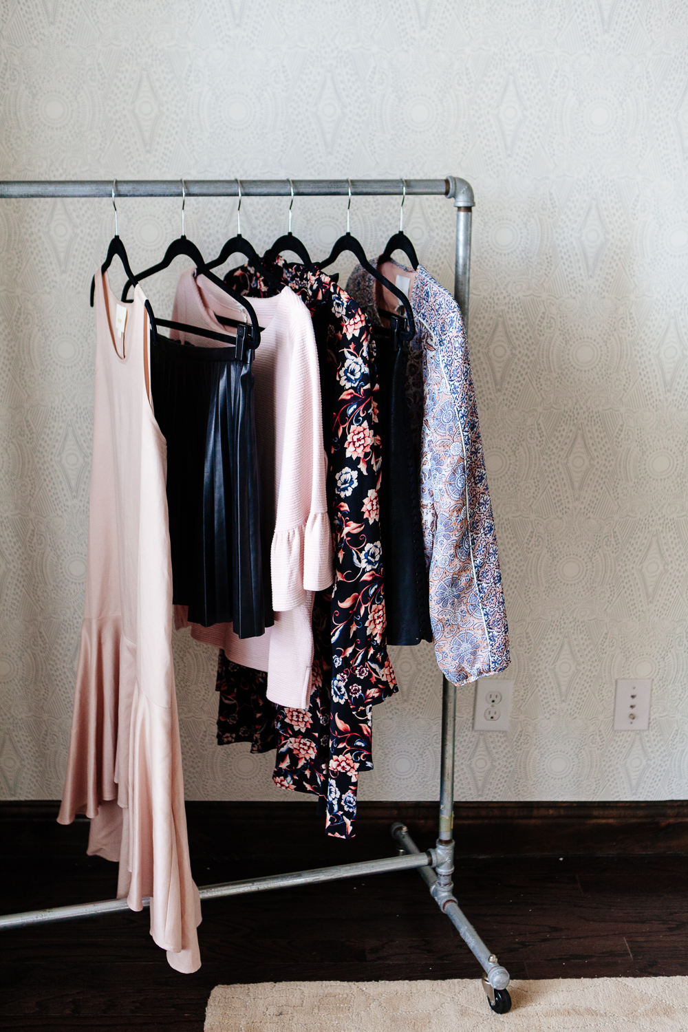 Clothing rack on wallpapered wall.