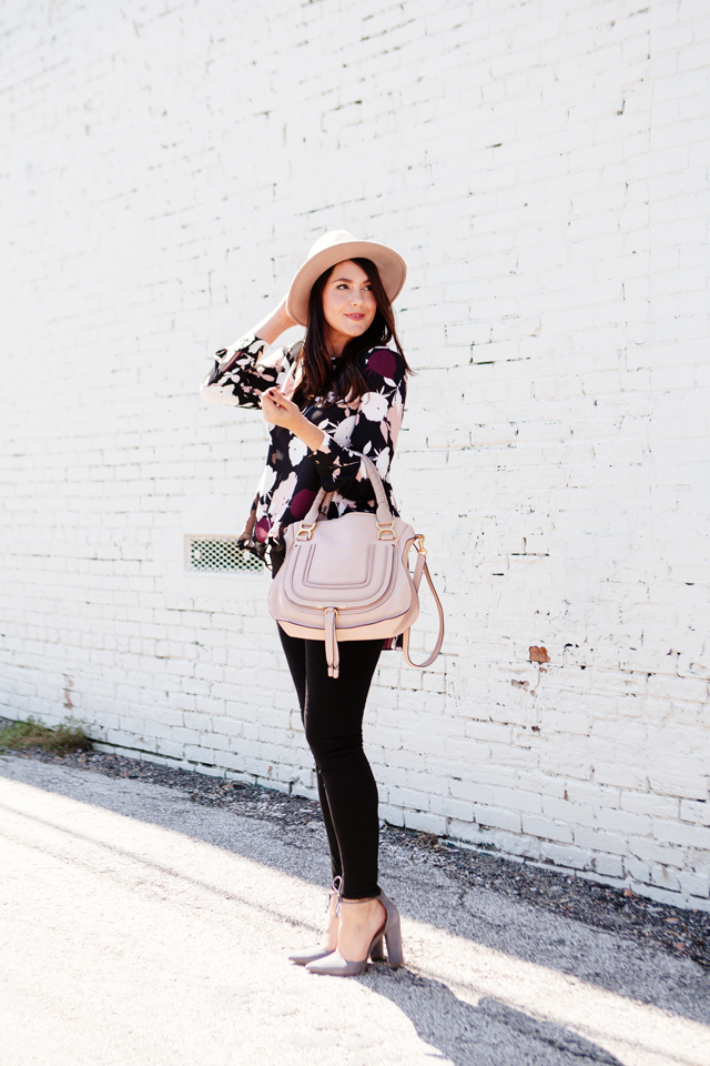 Floral blouse with black skinny jeans and blush hat and purse on Kendi Everyday