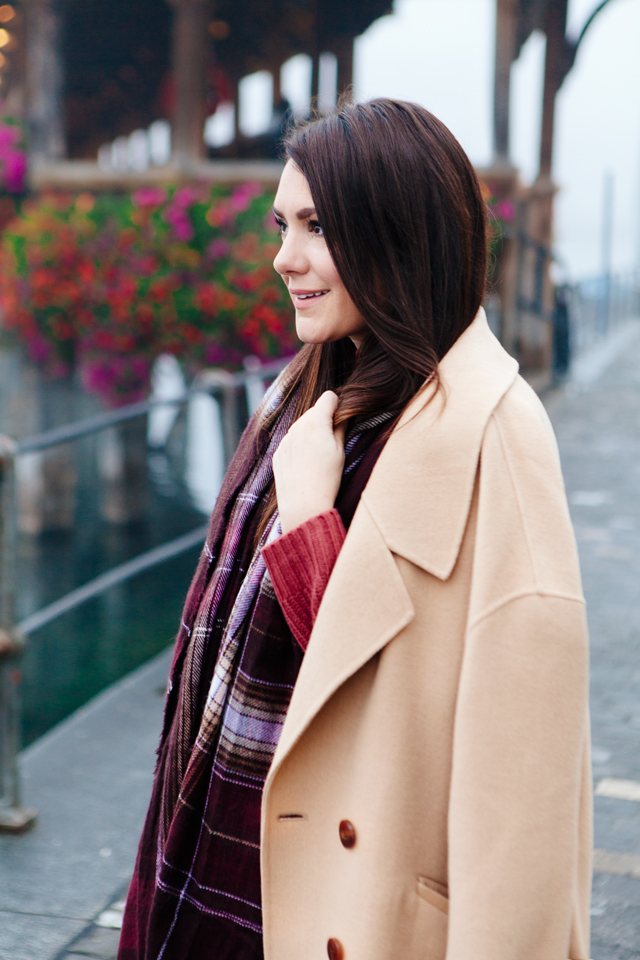 Burgundy sweater with plaid scarf and camel coat in Lucerne.