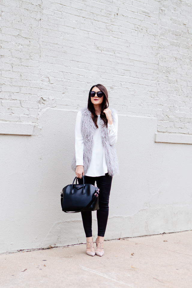 Grey faux fur vest with white blouse and black leggings outfit.