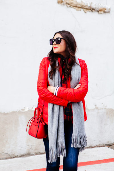 Bright red puffer jacket with layered plaid vest outfit.