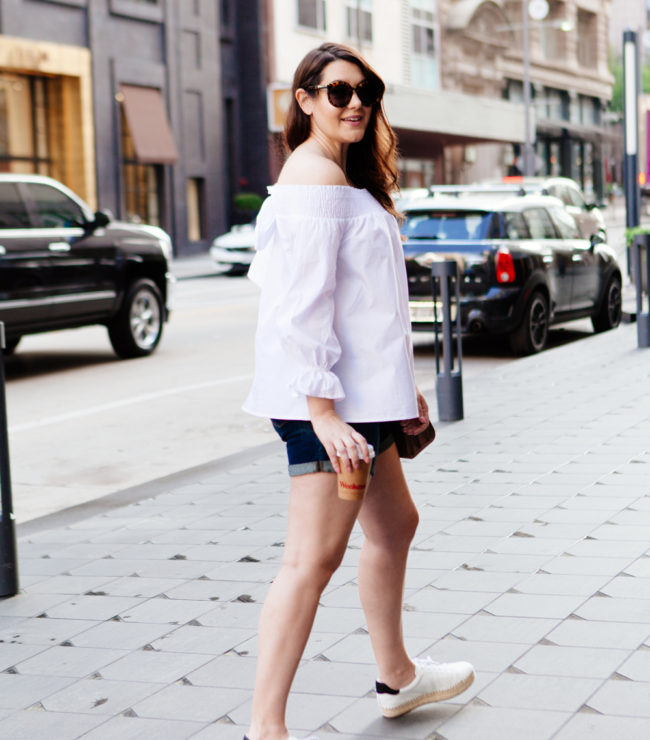 white off the shoulder top with cut offs and espadrille sneakers